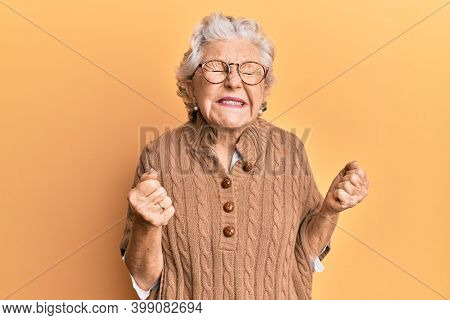Senior grey-haired woman wearing casual clothes and glasses very happy and excited doing winner gesture with arms raised, smiling and screaming for success. celebration concept.