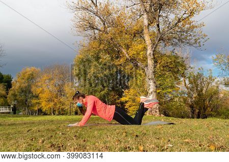 Sporty Dressed Woman Doing A Push-up On A Mat In The Park Wearing A Mask To Protect Herself From The