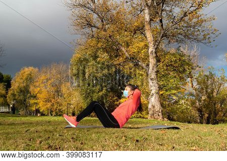 Sporty Dressed Woman Doing Sit-ups On A Mat In The Park Wearing A Mask To Protect Herself From The C