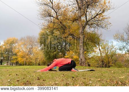 Sporty Dressed Woman Does Back Stretches On A Mat In The Park Wearing A Mask To Protect Herself From