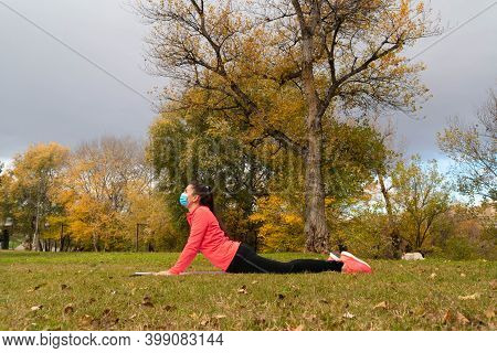 Sporty Dressed Woman Does Stretching And Yoga Positions On A Mat In The Park Wearing A Mask To Prote