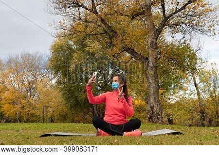Sporty Dressed Woman Sitting In The Lotus Flower Position On A Mat In The Park Wearing A Mask To Pro