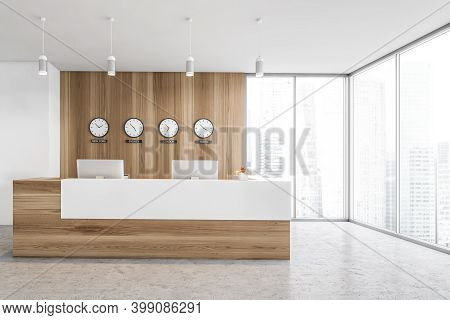 White And Wooden Reception Room With Desk, Computers And Clocks On Wooden Wall. Minimalist Reception
