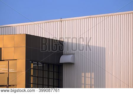Sunlight On Part Of Brown Modern Office On White Corrugated Metal Wall Of Industrial Building Agains