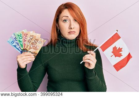 Beautiful redhead woman holding canadian dollars and canada flag skeptic and nervous, frowning upset because of problem. negative person.
