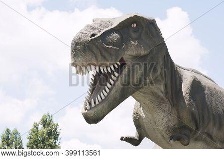 The Ancient Extinct Predator Tyrannosaurus Rex Dinosaur Is On Cloudy Sky Background.