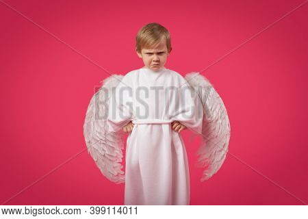 God Angel Gets Angry And Punishes With Glance. Child Boy Kid In Suit With Wings On Pink Solid Backgr