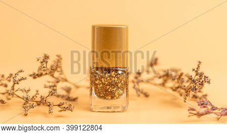 Nail Polish Of Beautiful Gold Colors On Orange Background.
