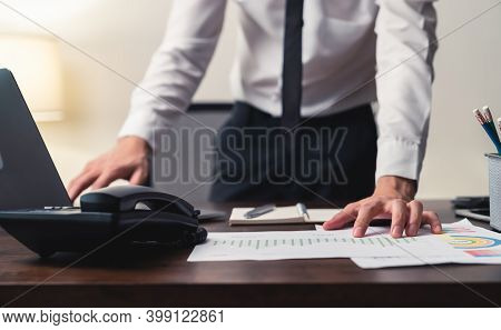 Businessman Standing And Working On Laptop With Note On Book In The Office At Night.