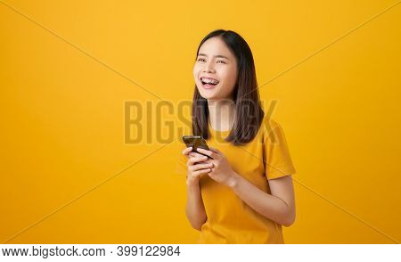 Cheerful Beautiful Asian Woman Holding Smartphone On Light Yellow Background.