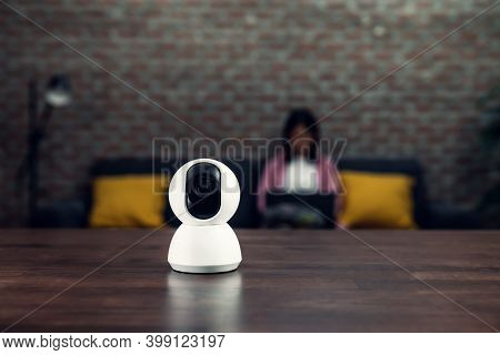 Security Cctv Camera, Surveillance Technology On The Table And Blur Background Woman Sitting On Sofa