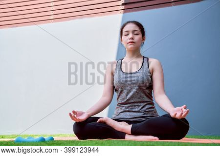 Woman Wearing Sportswear Practicing Yoga On Mat In House. Wellness Concept.