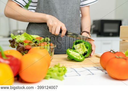 Close-up Of Woman Hands Use A Knife To Cut The Bell Pepper And Various Green Leafy Vegetables On The
