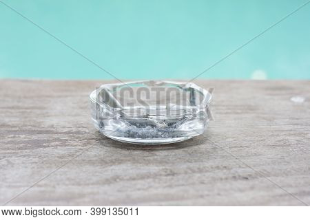 Cigarette Butts In Ashtray On Wooden Table.