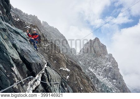 Male Alpinist In Sunglasses And Safety Helmet Holding Fixed Rope While Climbing Mountain. Mountainee