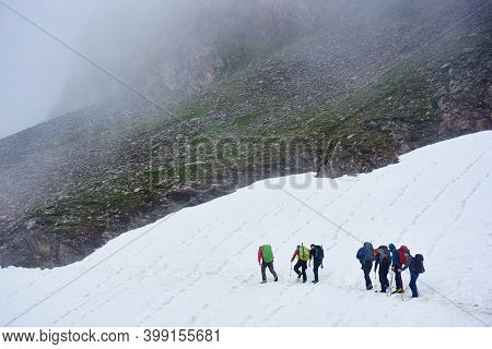Back View Of Travelers With Backpack Walking On Snow Covered Path While Hiking In Mountains. Male Mo