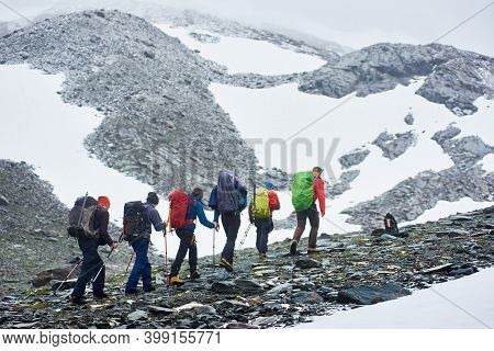 Back View Of Male Hikers With Backpacks Walking On Rocky Path In Winter Mountains. Group Of Mountain