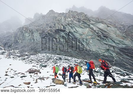Group Of Male Alpinists With Backpacks And Trekking Sticks Having Winter Hiking Tour In Mountains, W