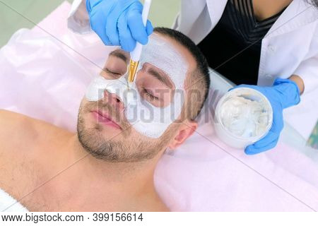 Cosmetologist Is Applying White Mask On Man Client Face Using Brush In Beauty Clinic. Portrait Of Gu
