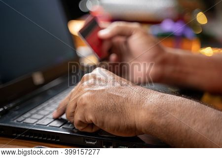 Close Up Of Old Man Hands Busy In Purchasing Or Doing Online Payment On Laptop During Holiday Season