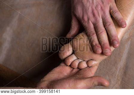 Massagist Scrubbing Womans Feet With Natural Scrub In Spa Salon. Procedure Of Peeling Body For Young