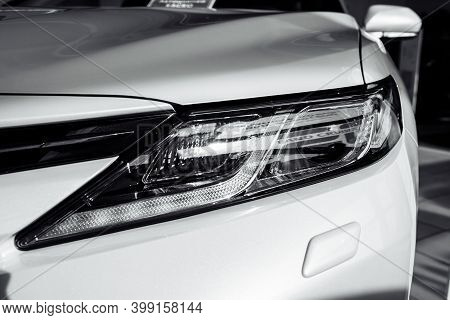 Headlight Of Modern Prestigious White Car Close Up. Close Up Photo Of Modern Car, Detail Of Headligh