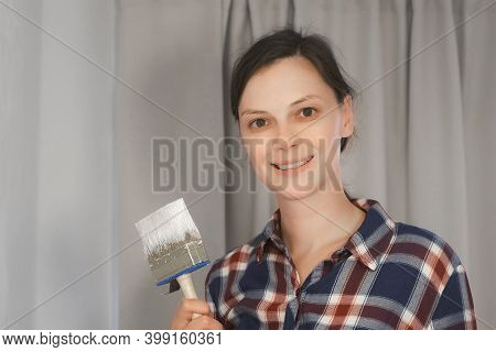 Portrait Of Woman House Painter Is Looking At Camera And Smiling Doing Renovation With Brush In Her