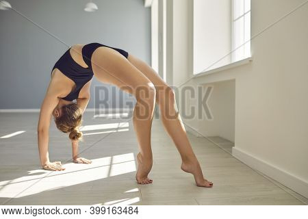 Gymnast Stands In The Position Of A Gymnastic Bridge On The Floor In A Bright Sunny Hall