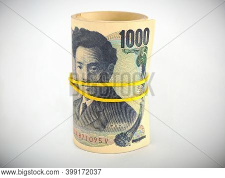 A Bundle Of Japanese 1000 Yen Bills Stands On A White Paper Background. Banknotes Are Rolled Up And
