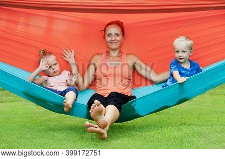Happy Family Have Fun On Tropical Beach Resort. Funny Kids With Young Mother Chilling In Swinging Ha