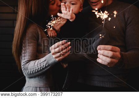 Portrait Of Happy Family, Mom, Dad And Baby Girl With Sparklers And Light. Family In Anticipation Of