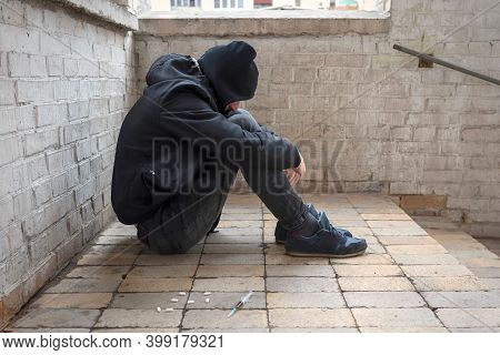 A Young Drug Addict In A Hood Sits In An Abandoned House After Taking Drugs. Addiction Concept. The