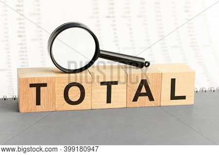 Wooden Blocks With The Text: Total With Magnifying Glass.