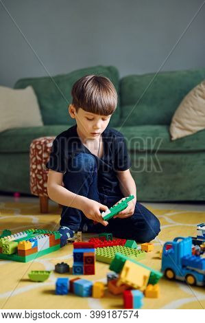 Preschool Caucasian Boy Playing With Constructor Sitting On The Floor, Lots Of Colorful Plastic Bloc