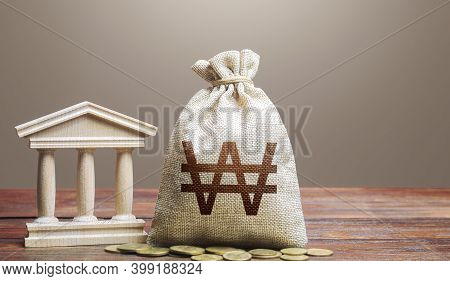 South Korean Won Money Bag And Bank / Government Building. Tax Collection And Budgeting. Monetary Po