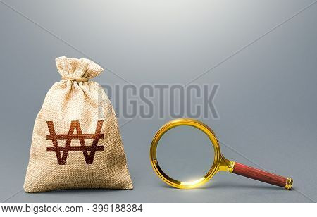 South Korean Won Money Bag And Magnifying Glass. Origin Of Capital And Legality Of Funds. Financial