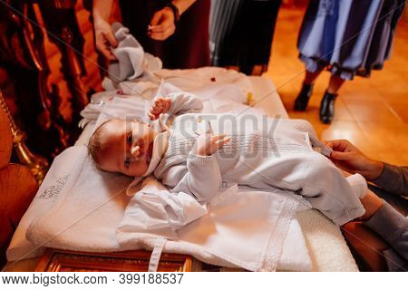 The Child Is Put On Clothes On A Table In The Church. The Ordinance Of Baptism.