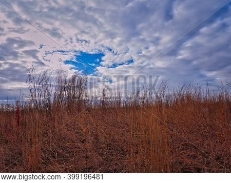 Late Autumn On The Prairie: Brilliant Sky Opens Up To Show Vibrant Blue Among Clouds Over The Prairi