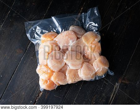 Vacuum Packed Scallops On A Wooden Background. Studio Closeup Of Scallops. Top View.