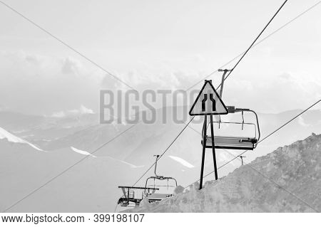 Warning Traffic Sign Road Narrows, Chairlift And High Snowy Mountains In Fog At Background. Caucasus