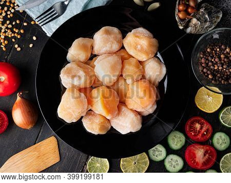 Scallops In A Black Plate With Ingredients. Studio Closeup Of Scallops. Top View.