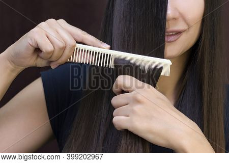 Beautiful Young Woman With Long, Smooth Brown Hair Looks After Her Hair. Combing Her Hair And Lookin