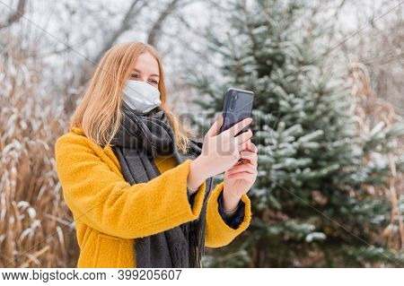 Young Blond Woman Wearing White Medical Face Mask Using Smart Phone App Over Nature Background, Tren
