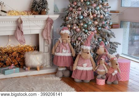 Interior With New Years Decorations And Xmas Tree. Cozy Room With Fireplace, Small Toy Reindeers And