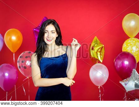 A Beautiful Woman Is Smiling Behind A Balloon On A Red Background.,happy New Year,merry Christmas