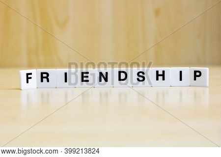 A Row Of Small White Plastic Tiles, Containing The Letters Forming The Word Friendship, To Represent