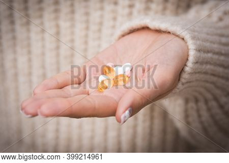 Woman Hand With Vitamins And Medication. Taking Vitamins And Supplements. B12, D3, Selenium