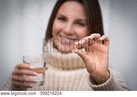 Young Beautiful Smiling Woman Holding Fish Oil Pill And A Glass Of Water. Taking Capsule With Omega