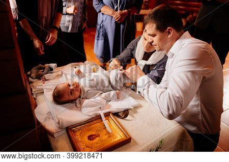 Parents Dress Their Child On A Table In The Church. The Ordinance Of Baptism.