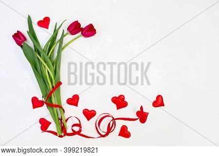 Beautiful Red Tulips And Satin Hearts On A White Textured Background With Copy Space. Concept Of Val